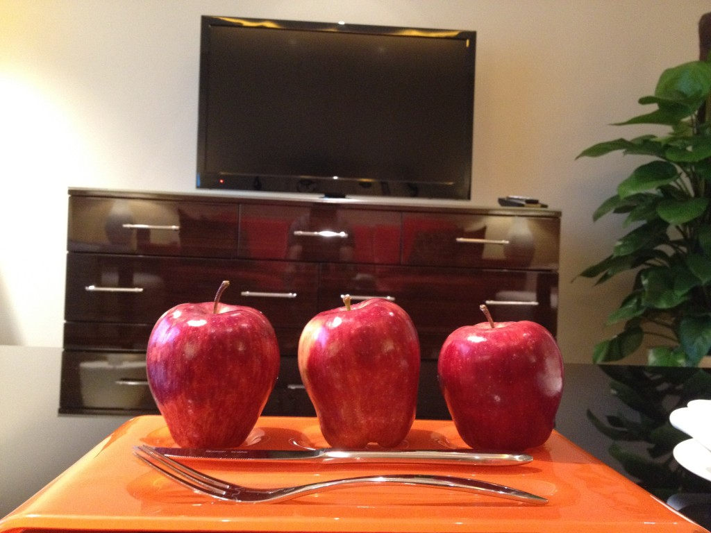 Three apples in the middle of the living room....and a TV.